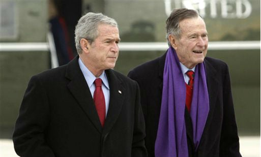 ©  In this Dec. 26, 2008 file photo, President George W. Bush walks with his father, former President George H.W. Bush, at Andrews Air Force Base, Md.