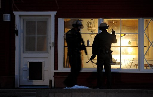 © Police officers check a house along Switzerland Avenue for murder suspect, former Los Angeles Police Department Officer Christopher Dorner, Thursday, Feb. 7, 2013, in Big Bear Lake, Calif.