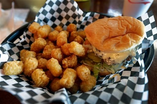 © This Wednesday, Feb. 6, 2013 photo shows a hamburger and tater tots at a restaurant in Charlotte, N.C. Deep-fried foods may be causing trouble in the Deep South.