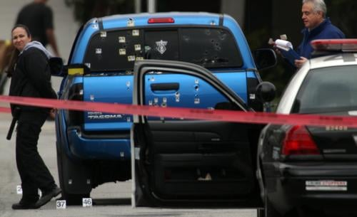 © Police investigators work around a blue pickup truck riddled with bullets in the 19500 block of Redbeam Avenue in Torrance after a police protection team fired on it. Photo Bob Chamberlin - Los Angeles Times