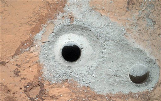 © This image released by NASA on Saturday Feb. 9, 2013 shows a fresh drill hole, center, made by the Curiosity rover on Friday, Feb. 8, 2013 next to an earlier test hole.