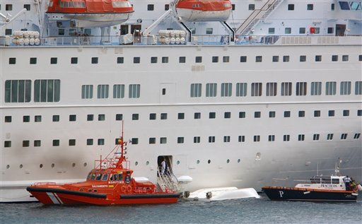 © An orange rescue boat docks by a capsized lifeboat from the British-operated cruise ship Thomson Majesty in Santa Cruz port of the Canary Island of La Palma, Spain, Sunday Feb. 10, 2013.