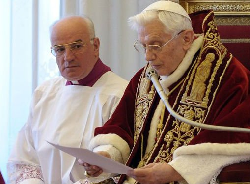 © In this photo provided by the Vatican newspaper L'Osservatore Romano, Mons. Franco Comaldo, left, a pope aide, looks at Pope Benedict XVI as he reads a document in Latin where he announces his resignation, during a meeting of Vatican cardinals.