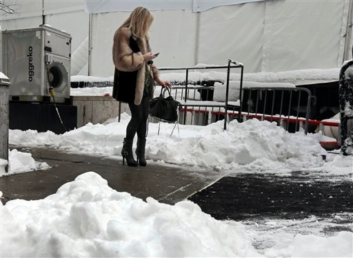 © A woman checks her mobile phone outside Lincoln Center, home of New York's Fashion Week shows, Saturday, Feb. 9, 2013. In New York City, the snow total in Central Park was 8.1 inches by 3 a.m. (AP Photo/Richard Drew)