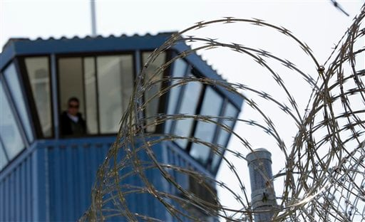 FILE - In this Aug. 17, 2011 file photo, concertina wire and a guard tower are seen at Pelican Bay State Prison near Crescent City, Calif.