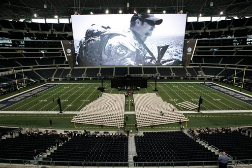 © A photo of Christopher Kyle is displayed on the large screen before the start of a memorial service for the former Navy SEAL at Cowboys Stadium, Monday, Feb. 11, 2013, in Arlington, Texas.