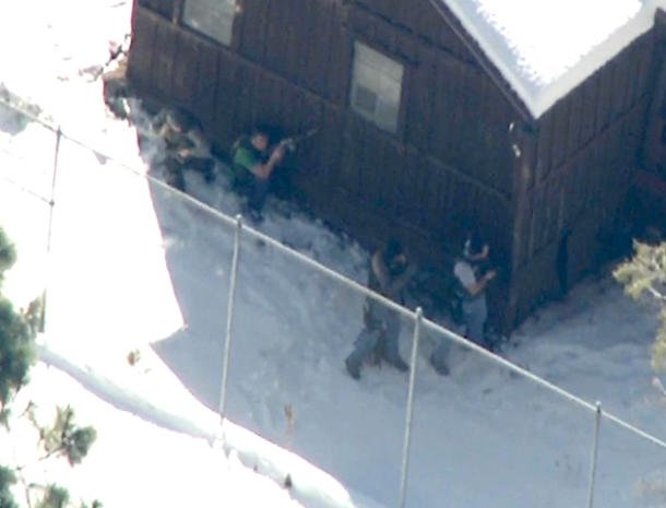 This CBSNews.com image shows law enforcement officers surrounding a location where Christopher Dorner was believed to be holed up.
