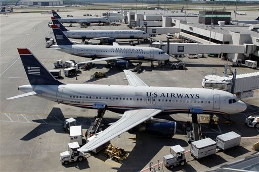 In this Thursday, Sept. 27, 2012, photo, US Airways jets are parked at their gates at the Charlotte/Douglas International airport in Charlotte, N.C. (AP Photo/Chuck Burton)