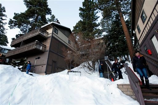 © Members of the news media are shown outside a home, at left, in Big Bear, Calif., where the owners of the cabin were taken hostage by fugitive Christopher Dorner