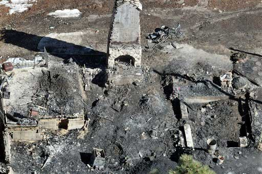 © In this aerial photo, law enforcement authorities investigate the charred remnants of a cabin Wednesday, Feb. 13, 2013 in the Angeles Oaks area of Big Bear, Calif.
