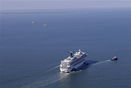 A disabled Carnival Lines cruise ship is towed to harbor off Mobile Bay, Ala., Thursday, Feb. 14, 2013. The ship with over 1,000 passengers aboard has been idled for nearly a week in the Gulf of Mexico following an engine room fire. (AP Photo)
