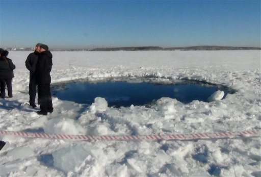 © A circular hole in the ice of Chebarkul Lake where a meteor reportedly struck the lake near Chelyabinsk, about 1500 kilometers (930 miles) east of Moscow, Russia, Friday, Feb. 15, 2013.