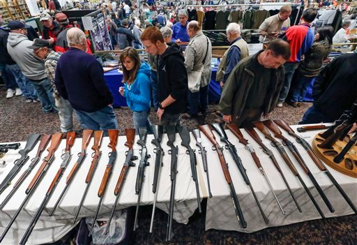 © In this Jan. 26, 2013, photo, guns are displayed on a table on display during the annual New York State Arms Collectors Association Albany Gun Show at the Empire State Plaza Convention Center, in Albany, N.Y.