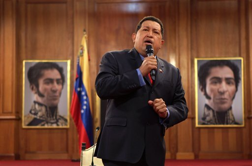 ©  In an Oct. 12, 2012 file photo Venezuela's President Hugo Chavez is flanked by portraits of Venezuelan independence hero Simon Bolivar, during a press conference at the Miraflores palace in Caracas, Venezuela.
