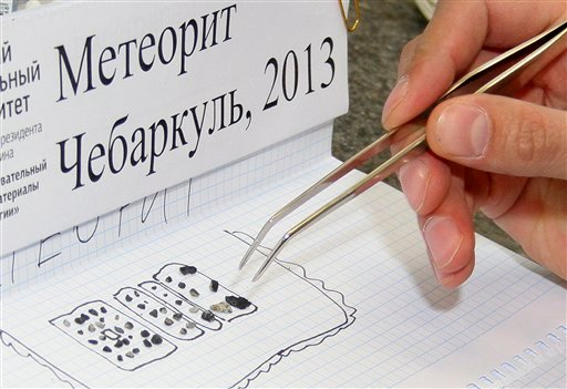 © In this photo distributed by the Urals Federal University Press Service a researcher examines pieces of a meteorite in a laboratory in Yekaterinburg on Monday, Feb.18, 2013.