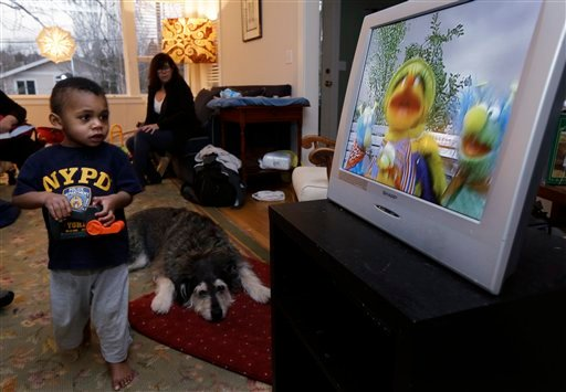 Nancy Jensen, second from left, looks on as her son Joe, 2, is given a special treat of a little TV time Tuesday, Feb. 12, 2013 at their home in Seattle. (AP)