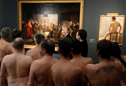 """In this Monday, Feb. 18, 2013 photo, Naked Museum visitors look at pictures of the show """"Nude Men from 1800 to Today"""" during a special opening to friends of nudism at the Leopold Museum, Vienna, Austria."""