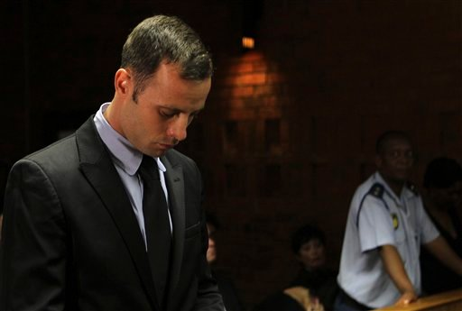Olympic athlete Oscar Pistorius stands inside the court as a police officer looks on during his bail hearing at the magistrate court in Pretoria, South Africa, Wednesday, Feb. 20, 2013. (AP Photo/Themba Hadebe)