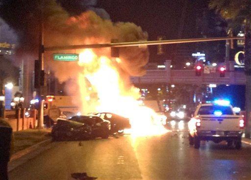 © Smoke and flames billow from a burning vehicle following a shooting and multi-car accident on the Las Vegas Strip in Las Vegas early Thursday, Feb. 21, 2013.