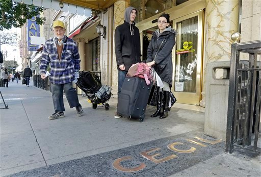 A man, left, leaves the Cecil Hotel with belongings as Michael and Sabina Baugh, both 27, of Plymouth, England, wait for transportation as they leave the hotel in downtown Los Angeles Wednesday, Feb. 20, 2013. (AP Photo/Reed Saxon)