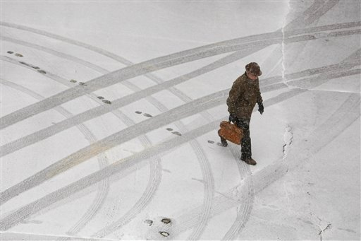 A man walks in the snow, Wednesday, Feb. 20, 2013 in Tulsa, Okla. (AP Photo/Tulsa World, Tom Gilbert)