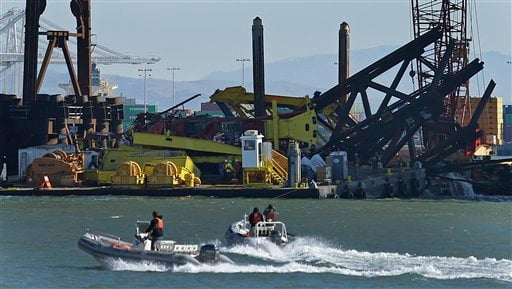 Investigators approach the scene where a crane overturned onto a barge and into San Francisco Bay, seen from Clipper Cove on Treasure Island Thursday, Feb. 21, 2013, in San Francisco. (AP)