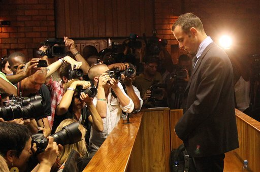© Photographers take photos of Olympic athlete Oscar Pistorius as he stands in the dock during his bail hearing at the magistrates court in Pretoria, South Africa, Friday, Feb. 22, 2013.