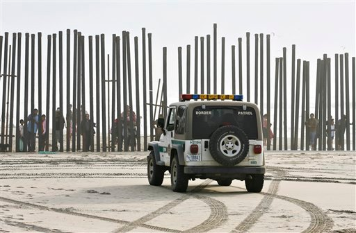 ©  In this Jan. 18, 2009 file photo, a U.S. Border Patrol vehicle sits parked in front of a crowd of people peering through the U.S.-Mexico border fence at Border Field State Park in San Diego.