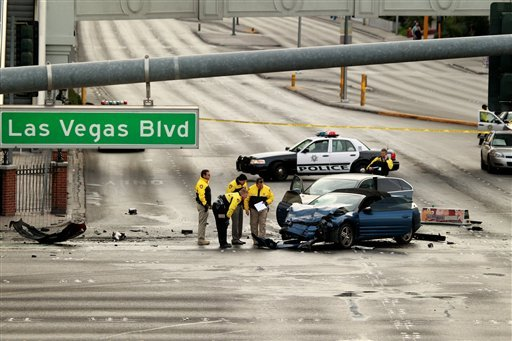 ©  In this Feb. 21, 2013 file photo, law enforcement personal investigate the scene of a mulit-vehicle accident on Las Vegas Blvd and Flamingo Road.