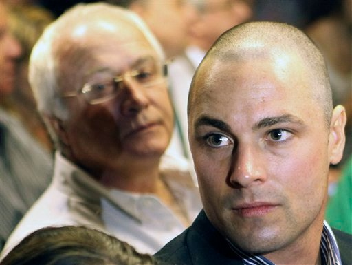 ©  In this Feb. 19, 2013 file photo, Carl Pistorius, right, and Henke Pistorius, the brother and father of Olympic athlete Oscar Pistorius, charged with the shooting death of his girlfriend attend Oscar's bail hearing at the magistrate court in Pretoria.