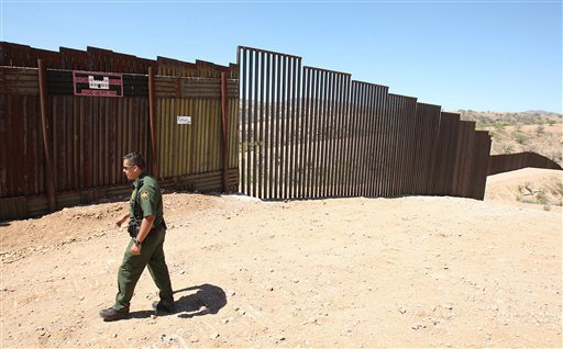 In this June 19, 2008 file photo, U.S. Border Patrol agent Santos Flores walks in front of a section of old border fence, left, where it meets a five-mile section of new border fence at the border in Nogales, Ariz.