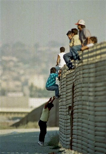 In this Oct. 14 1991 file photo, a group of illegal Mexican immigrants jump from a border fence to enter the United States, near Tijuana, Mexico.