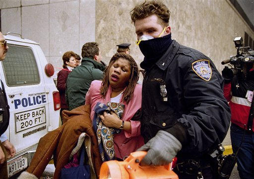 © In this file photo of Feb. 26, 1993, a New York City police officer leads a woman to safety following a bomb blast at the World Trade Center.