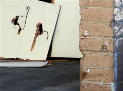 A bullet riddled garage door and wall is seen in Santa Cruz, Calif., on Wednesday, Feb. 27, 2013 where a suspected murderer was shot Tuesday afternoon after he allegedly killed two Santa Cruz Police Department detectives. (AP Photo/Thomas Mendoza)