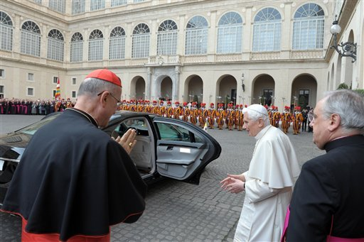 © In this photo provided Friday, March 1, 2013, then Pope Benedict XVI is saluted by Cardinal Tarcisio Bertone, left, as leaves Piazza San Damaso inside the Vatican.