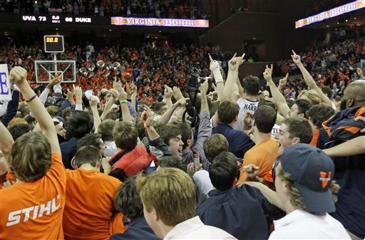 In this Feb. 28, 2013 photo, fans celebrate Virginia's win over Duke by storming the court in Charlottesville, Va. Virginia won the game 73-68. (AP Photo/Steve Helber, File)