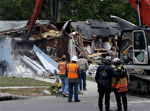© Demolition experts watch as the home of Jeff Bush, 37, is destroyed Sunday, March 3, 2013, after a sinkhole opened up underneath it late Thursday evening swallowing Bush, 37, in Seffner, Fla.