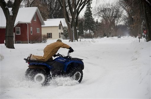 Eric, a Moorhead, Minn. man who did not give his last name, plays with an ATV after a snowstorm left city streets slick on Monday, March 4, 2013. (AP Photo/Minnesota Public Radio, Nathaniel Minor)