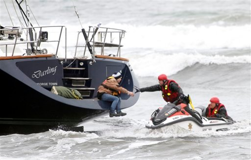 © Rescuers attempt to grab a woman off the back of the 82-foot-long sailboat, the Darling, stuck in the surf off Pacifica, Calif., Monday March 4, 2013.