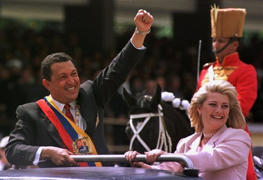 FILE - In this Feb. 4, 1999 file photo, Venezuela's newly sworn in President Hugo Chavez salutes the crowd next to his wife Marisabel Chavez during a military parade commemorating the seventh anniversary of his failed 1992 coup in Caracas, Venezuela. (AP)
