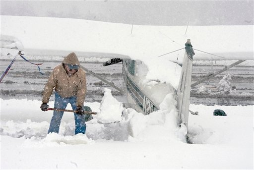Pilot John Harsh shovels snow off of the tail of his Cessna 172 airplane at the Shenandoah Valley Regional Airport during heavy snow Wednesday, March 6, 2013 in Weyers Cave, Va. (AP Photo/The Daily News-Record, Michael Reilly)