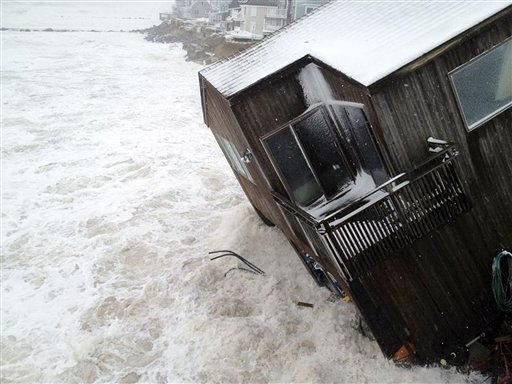 House on the Plum Island seacoast in Newbury, Mass., sits partially collapsed into the churning surf, driven by winds from a storm centered far out in the Atlantic Ocean at high tide March 8, 2013. (AP Photo/Newburyport Daily News, Mac Cerullo)