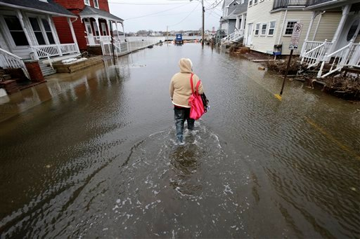 Carol Marelli walks down her flooded street Thursday, March 7, 2013, in Sea Bright, N.J., after an overnight storm. (AP Photo/Mel Evans)