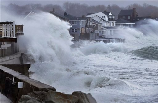 Ocean waves crash over a seawall and into houses along the coast in Scituate, Mass., Thursday, March 7, 2013. (AP Photo/Steven Senne)