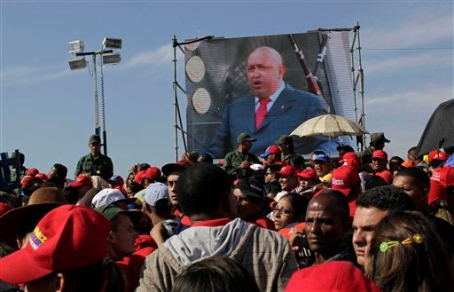 Screen showing of Venezuela's President Hugo Chavez plays in front of the site where Chavez's funeral ceremony will take place as people gather outside the military academy in Caracas, Venezuela March 8, 2013. (AP Photo/Rodrigo Abd)