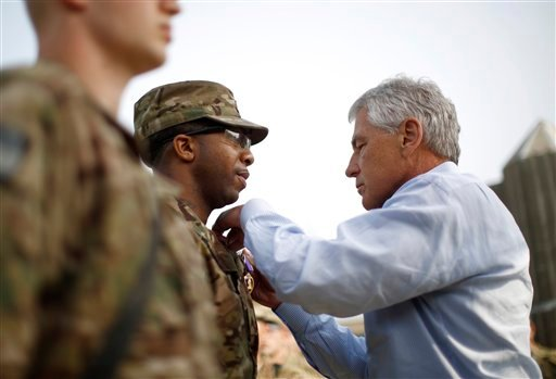 © U.S. Defense Secretary Chuck Hagel participates in the awarding of a Purple Heart to Sgt. Jeremyah Williams of the 426 Brigade Support Battalion, at Jalalabad Airfield in eastern Afghanistan, Saturday, March 9, 2013.