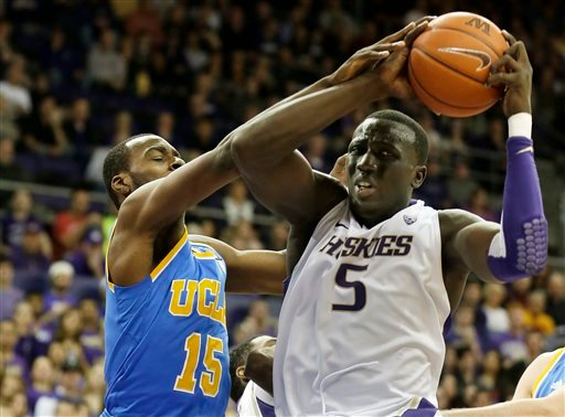 © Washington's Aziz N'Diaye (5) battles for the ball with UCLA's Shabazz Muhammad during the first half of an NCAA college basketball game, Saturday, March 9, 2013, in Seattle. (AP Photo/Ted S. Warren)