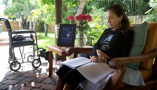 © In this Dec. 31, 2012 photo, Susan Spencer-Wendel sits in her backyard at her home in West Palm Beach, Fla., reading a printed copy of her book.