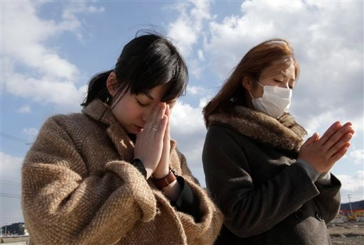 © People offer prayer in a moment of silence in front of what is left of a disaster control center in an area devastated by the March 11, 2011 earthquake and tsunami in Minamisanriku, Miyagi Prefecture, Monday, March 11, 2013.