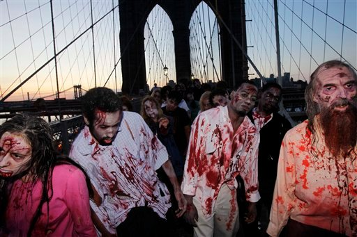"""© Costumed actors, promoting the Halloween premiere of the AMC television series """"The Walking Dead"""", shamble along the Brooklyn Bridge while posing for pictures in New York, in this Oct. 26, 2010 file photo."""